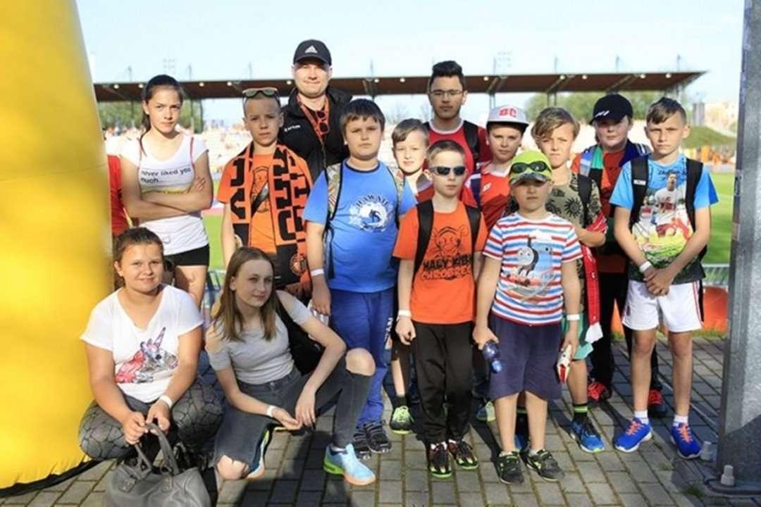 Grupa dzieci uczesticzących w projekcie wraz z trenerem na stadionie