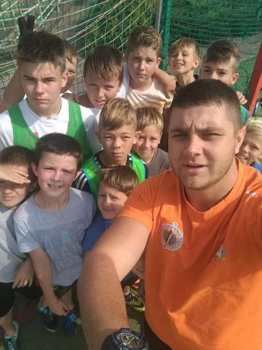 Grupa dzieci uczestniczących w projekcie wraz z trenerem.