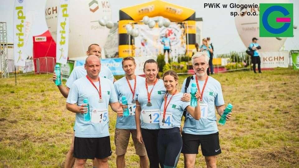 Zawodnicy PWiK pozują do zdjęcia z medalami i formowymi bidonami na wodę z kranu.