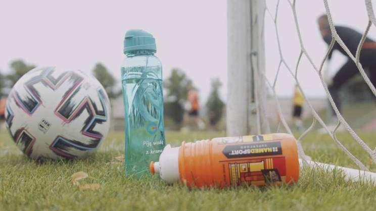 Na zdjęciu piłka nożna i dwa bidony z wodą. Zdjęcie wykonane podczas kręcenia spotu promującego picie głogowskiej kranówki.