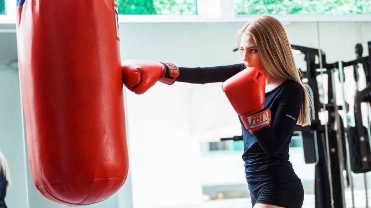 Na zdjęciu młoda kobieta trenuje boks - w rękawicach uderza w worek bokserski.