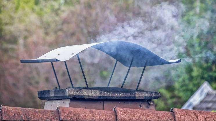 Na zdjęciu widać dymiący komin w domku jednorodzinnym.