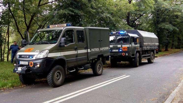 dwa pojazdy saperskie oznakowane, oczekujące na poboczu drogi. W tle drzewa.