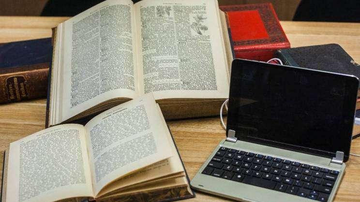 zdjęcie przedstawia otwarte ksiązki i laptopa