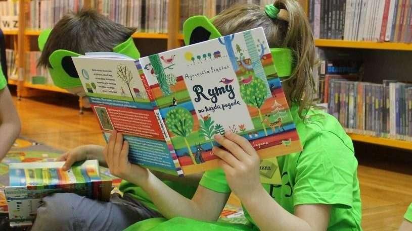 na zdjęciu dziecko czytające książkę w miejskiej bibliotece publicznej w Głogowie