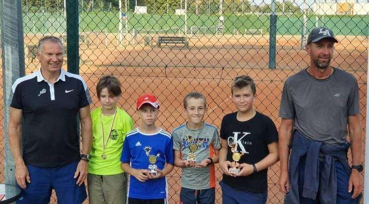 Na zdjęciu czwórka nagrodzonych dzieci i dwóch trenerów podczas tenisowego turnieju o puchar prezydenta w Głogowie