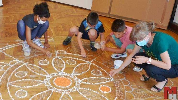 na zdjęciu czwórka dzieci podczas wykonywania pracy plastycznej w ramach akcji wakacje w muzeum