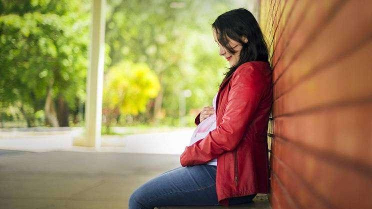 na zdjęciu kobieta w ciąży siedząca na ławce