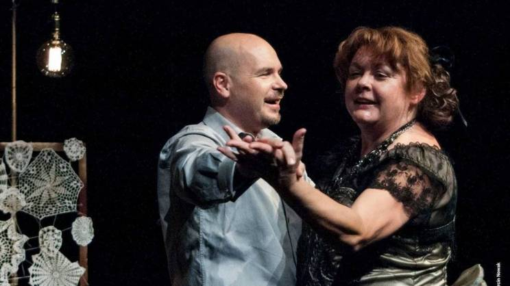 na zdjęciu mężczyzna i kobieta trzymają się za ręce i tańczą