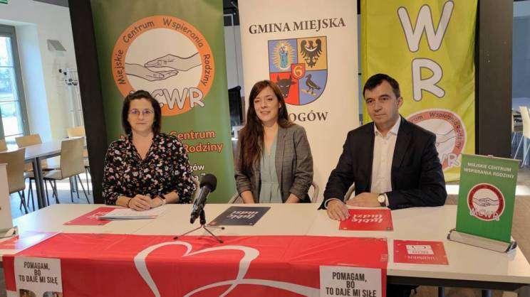 na zdjęciu prezydent Głogowa, lider szlachetnej paczki oraz wolontariuszka. Wszyscy siedzą przy stole podczas konferencji prasowej na temat szlachetnej paczki w Głogowie